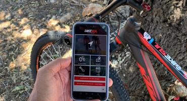 ciclista a mostrar app da bikesul com bicicleta ktm no fundo
