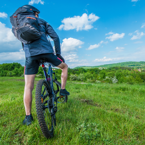 cyclist with backpack on his back pedaling in a green field