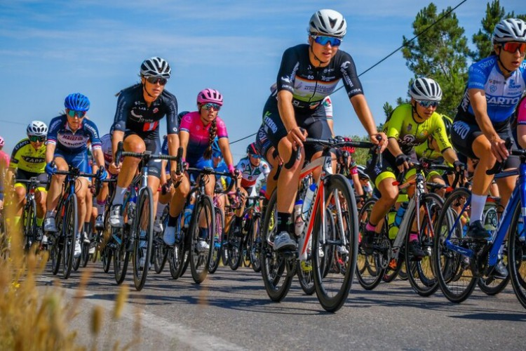 ciclistas femininas  com o arco do triunfo em França como fundo