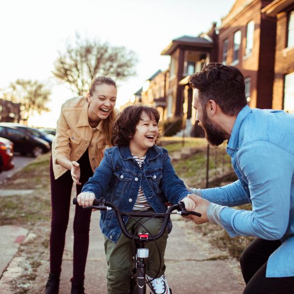 menino a andar de bicicleta com os pais