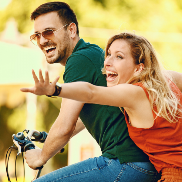 couple riding a bike and smiling