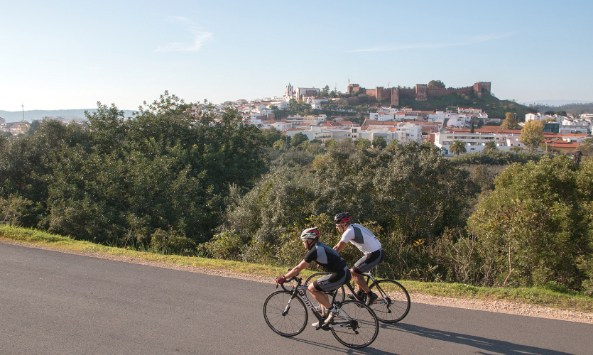 Two cyclists riding in Silves, with the Castle in the back