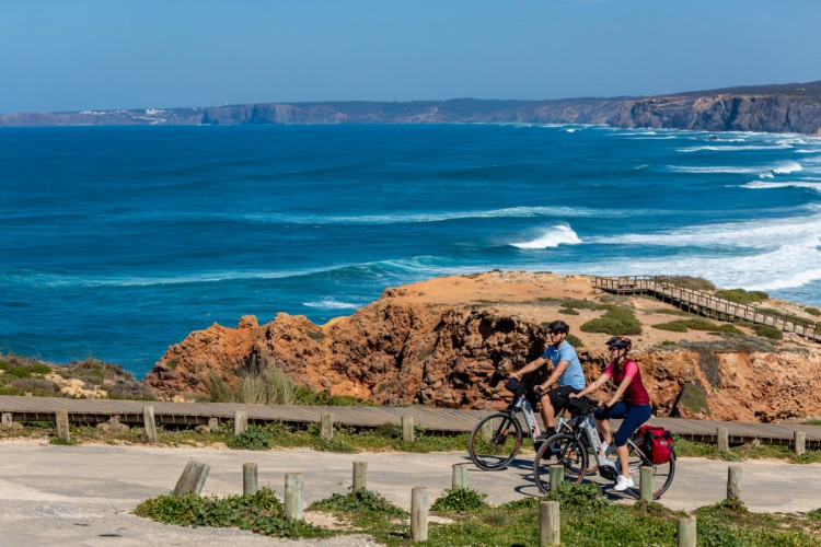 two cyclists pedaling with a sea view