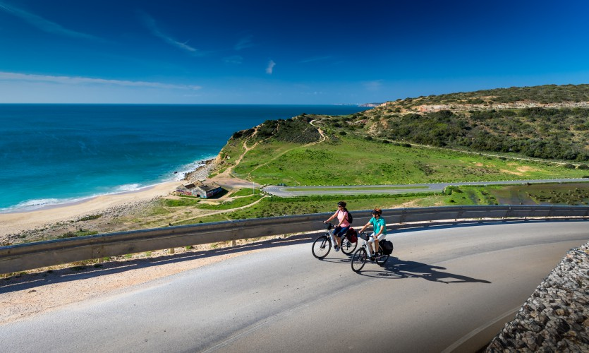 A couple is pedalling near the sea in the Algarve