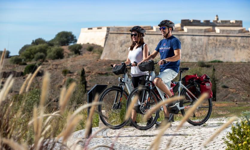 Um casal num passeio de bicicleta junto ao forte de Castro Marim